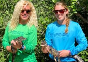Picture of two women holding baby alligators