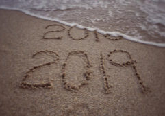 '2019' formed on background of beach sand. With blurred vintage styled background.